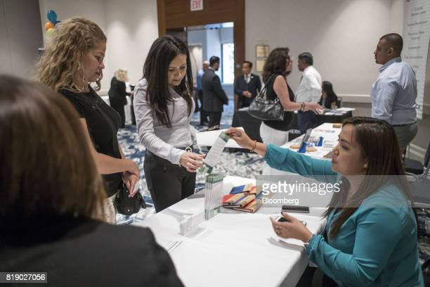 Job seekers left speak with a recruiter during a CoasttoCoast career fair in San Jose California US on Wednesday July 19 2017 The US Department of...