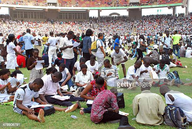 Job seekers pass an exam as they apply for work with immigration departement on the pitch of Abuja National Stadium on March 15 2014 At least seven...
