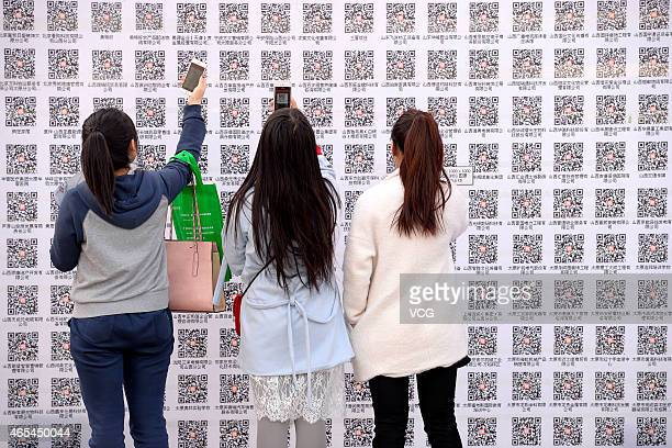 Job seekers scan QR codes during the 2nd Shanxi Exhibition Hall Job Fair on March 6 2015 in Taiyuan Shanxi province of China A new mode of 'Offline 2...
