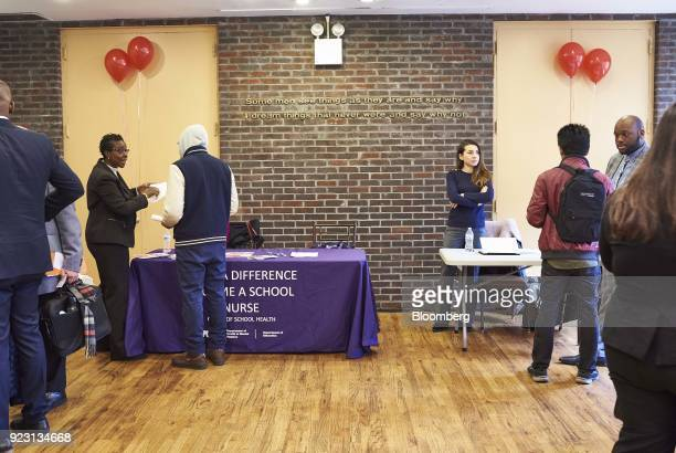 Job seekers speak with representatives during a Shades of Commerce Career Fair in the Brooklyn borough of New York US on Saturday Feb 17 2018 The...