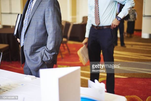Job seekers stand in line to speak with a representative during a National Career Fair event in Edison New Jersey US on Thursday Sept 20 2018 Filings...
