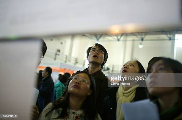 Job seekers view posted information at a job fair for postgraduate students on December 14 2008 in Beijing China Nearly 40000 applicants competed for...