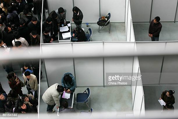 Job seekers visit a job fair for graduating university students at the Qujiang International Convention and Exhibition Center on February 28 2009 in...