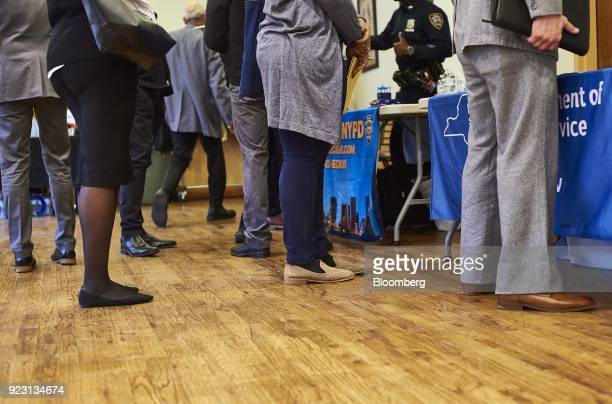 Job seekers wait in line to speak with representative during a Shades of Commerce Career Fair in the Brooklyn borough of New York US on Saturday Feb...