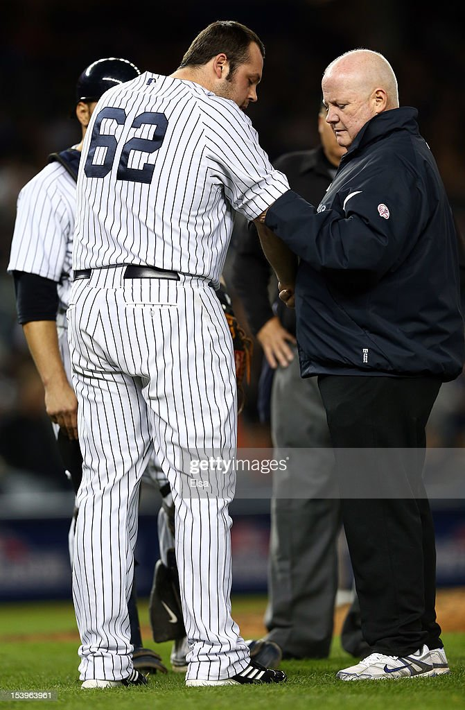 Joba Chamberlain #62 of the New York Yankees receives medical attention after being hit by a broken bat during Game Four of the American League Division Series against the Baltimore Orioles at Yankee Stadium on October 11, 2012 in the Bronx borough of New York City.