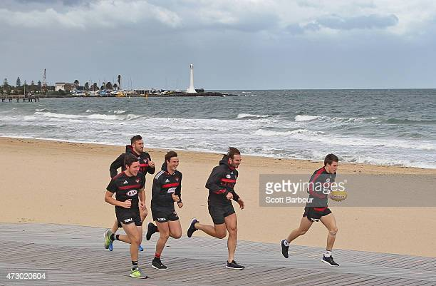 Jobe Watson captain of the Bombers runs with his teammates along the beach during an Essendon Bombers AFL recovery session at St Kilda Sea Baths on...
