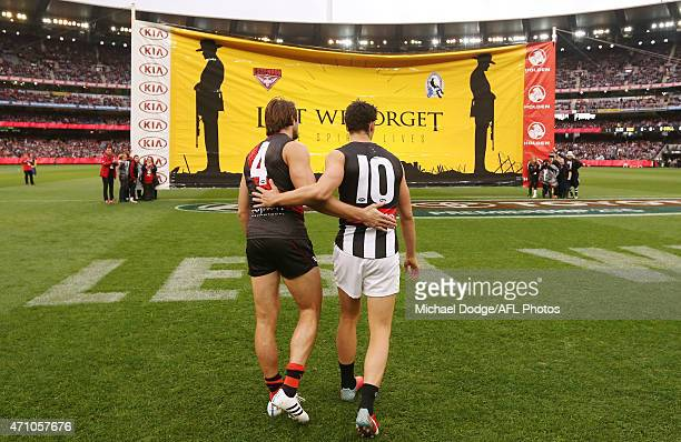 Jobe Watson of the Bombers and Scott Pendlebury of the Magpies walk arm in arm to the Anzac banner during the round four AFL match between the...