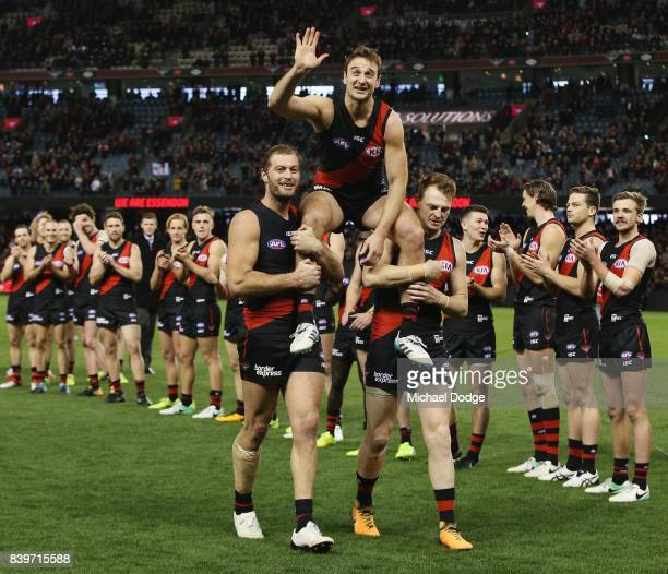 Jobe Watson of the Bombers gets carried off for his last home match by Tom Bellchambers and Brendon Goddard during the round 23 AFL match between the...