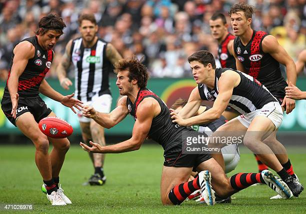 Jobe Watson of the Bombers handballs whilst being tackled by Jack Crisp of the Magpies during the round four AFL match between the Essendon Bombers...