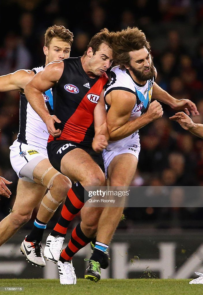 Jobe Watson of the Bombers is bumped by Justin Westhoff of the Power which injures his shoulder during the round 15 AFL match between the Essendon Bombers and Port Adelaide Power at Etihad Stadium on July 7, 2013 in Melbourne, Australia.