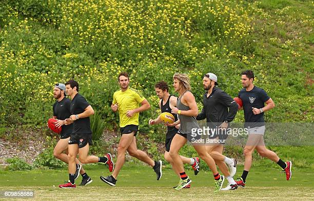 Jobe Watson runs with his teammates after speaking to the media about his AFL playing future during an Essendon Bombers AFL media session at St...