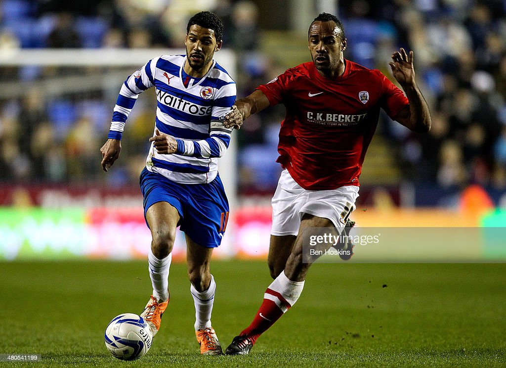 Jobi McAnuff of Reading holds off pressure from Chris O'Grady of Barnsley during the Sky Bet Championship match between Reading and Barnsley at Madejski Stadium on March 25, 2014 in Reading, England,