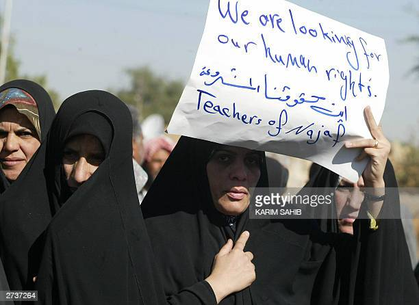 Jobless Shiite teachers from Najaf hold up a placard 17 November 2003 as they demonstrate in front of the Coalition Provisional Authority...