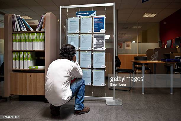 A jobseeker checks employment vacancies on a display board inside a job center also known as Pole Emploi the French national employment center in...