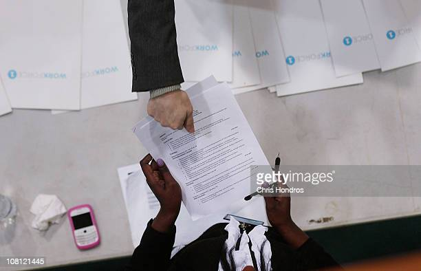 A jobseeker hands his resume to Candice Perkins a representatvie of Workforce1 an citysponsored employment agency during a 'Work Search' event aimed...