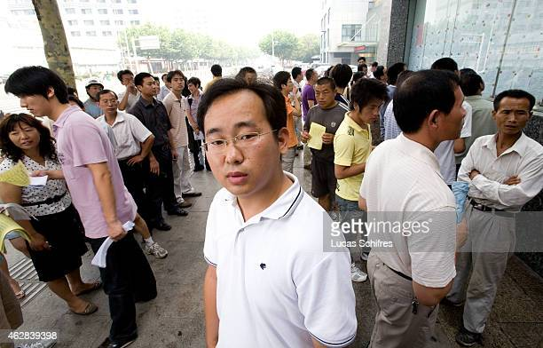 Jobseeker Xie Keyan poses for a photograph while other jobseekers look at job offers on the wall on an employment center on June 27 2009 in Jiangyin...