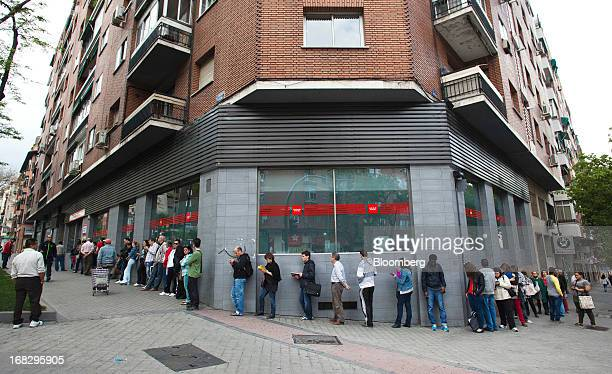 Jobseekers are seen waiting in a queue outside an employment office before the opening in Madrid Spain on Wednesday May 8 2013 Spanish unemployment...