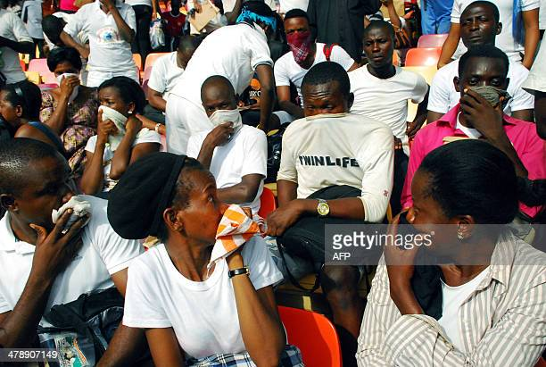 Jobseekers cover their nose and mouth for safety after security agents from the immigration services threw a cannister of tear gas to disperse the...