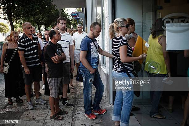 Jobseekers pass through the doors of a Labor Force Employment Organisation job center soon after opening in Athens Greece on Tuesday Aug 20 2013...