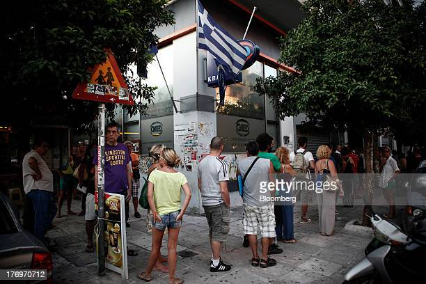 Jobseekers stand beneath a Greek national flag as they queue to enter a Labor Force Employment Organisation job center in Athens Greece on Tuesday...