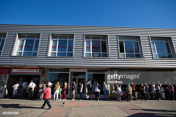 Jobseekers wait in a long queue outside an employment center before opening in Madrid Spain on Wednesday July 23 2014 While unemployment figures...