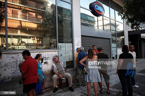 Jobseekers wait outside the closed shutters of a Labor Force Employment Organisation job center ahead of opening in Athens Greece on Tuesday Aug 20...
