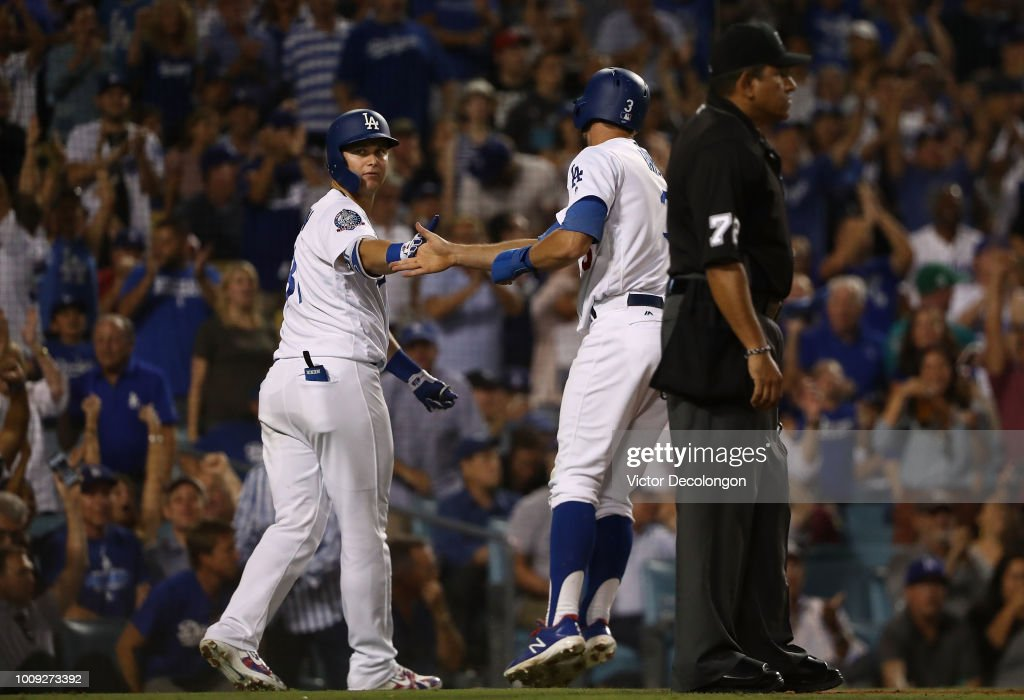 Joc Pederson #31 and Chris Taylor #3 of the Los Angeles Dodgers celebrate at home plate after Taylor scored on a bunt single by teammate Enrique 'Kike' Hernandez #14 (not in photo) during the seventh inning of the MLB game against the Milwaukee Brewers at Dodger Stadium on August 1, 2018 in Los Angeles, California.