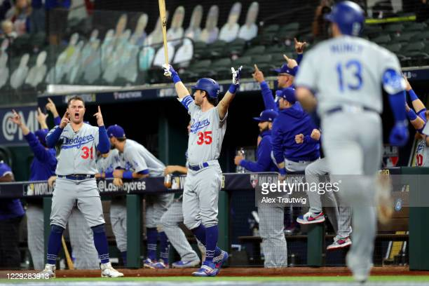Joc Pederson and Cody Bellinger of the Los Angeles Dodgers react to a Max Muncy solo home run in the fifth inning during Game 5 of the 2020 World...