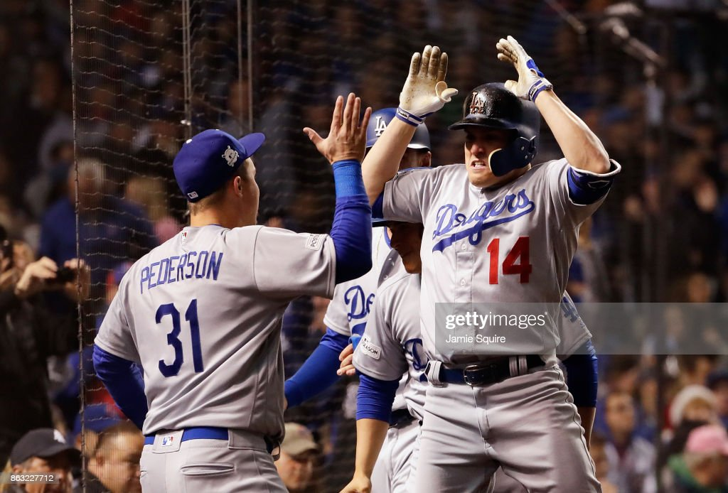 Joc Pederson #31 and Enrique Hernandez #14 of the Los Angeles Dodgers celebrate after Hernandez hit a grand slam in the third inning against the Chicago Cubs during game five of the National League Championship Series at Wrigley Field on October 19, 2017 in Chicago, Illinois.