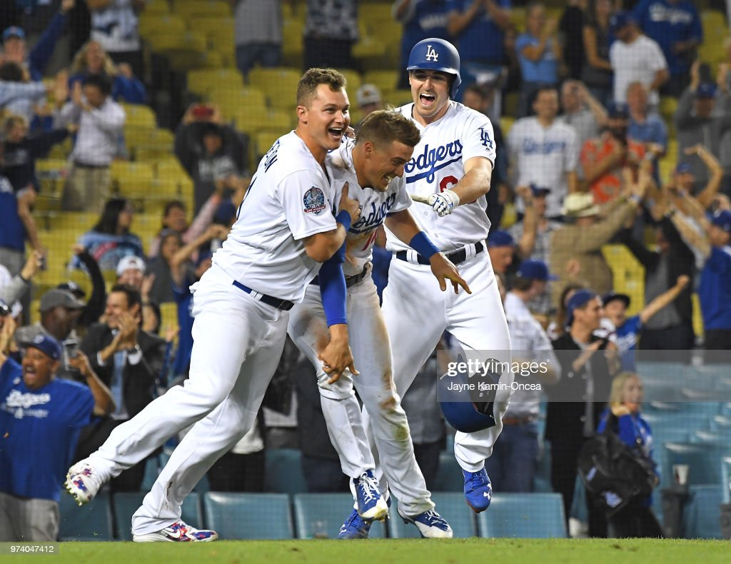 Joc Pederson #31 and Ross Stripling #68 celebrate with Enrique Hernandez #14 of the Los Angeles Dodgers as they defeated the Texas Rangers in the eleventh inning at Dodger Stadium on June 13, 2018 in Los Angeles, California.