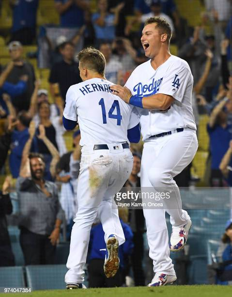 Joc Pederson celebrates with Enrique Hernandez of the Los Angeles Dodgers as they defeated the Texas Rangers in the eleventh inning at Dodger Stadium...