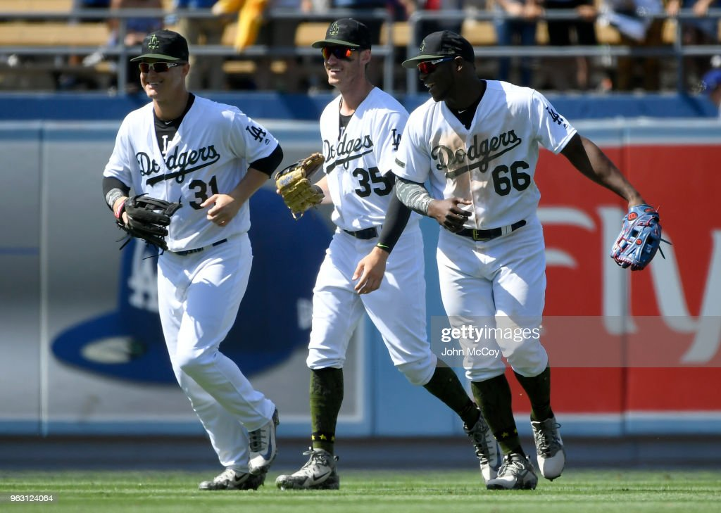 Joc Pederson #31, Cody Bellinger #35 and Yasiel Puig #66 of the Los Angeles Dodgers celebrate after the final out against the San Diego Padres at Dodger Stadium on May 27, 2018 in Los Angeles, California. Dodger won 6-1.