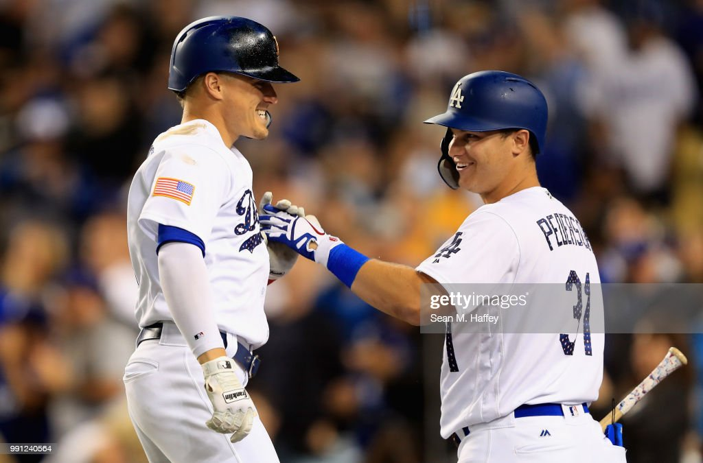 Joc Pederson #31 congratulates Enrique Hernandez #14 of the Los Angeles Dodgers after his two-run homerun during the sixth inning of a game against the Pittsburgh Pirates at Dodger Stadium on July 3, 2018 in Los Angeles, California.