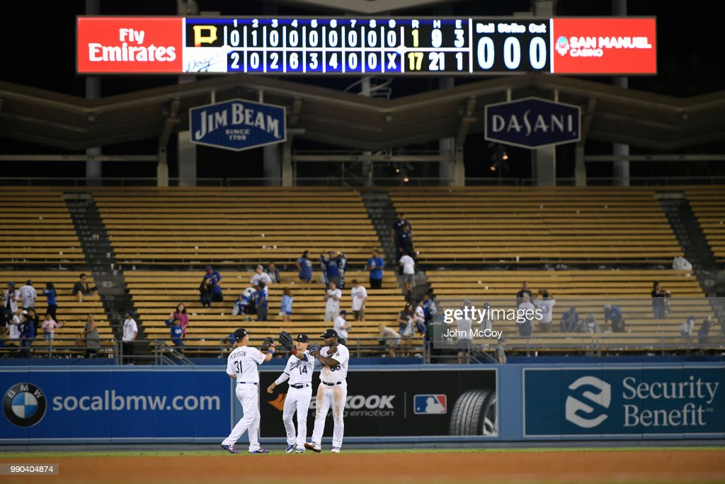 Joc Pederson #31, Enrique Hernandez #14 and Yasiel Puig #66 of the Los Angeles Dodgers celebrate at the end of a 17-1 win over the Pittsburgh Pirates at Dodger Stadium on July 2, 2018 in Los Angeles, California.