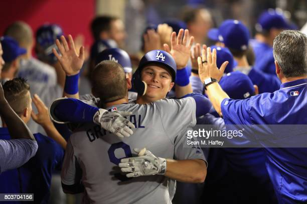 Joc Pederson hugs Yasmani Grandal of the Los Angeles Dodgers after hitting a threerun homerun during the sixth inning of a game against the Los...