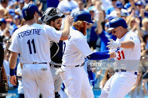 Joc Pederson is congratulated at the plate by Justin Turner and Logan Forsythe of the Los Angeles Dodgers after hitting a grand slam during the third...