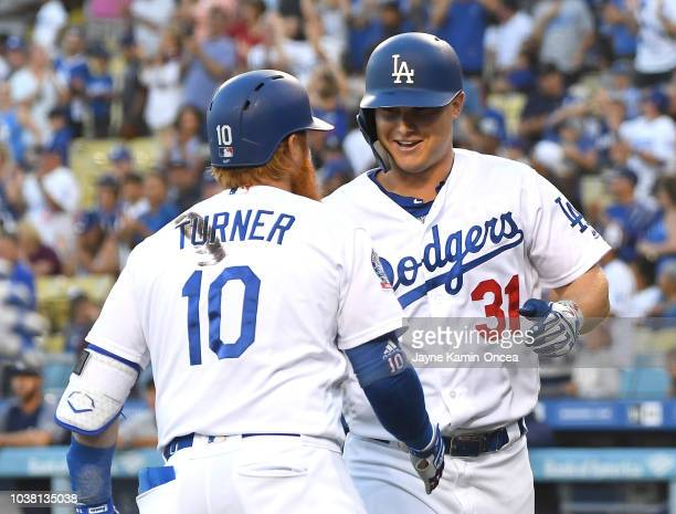 Joc Pederson is congratulated by Justin Turner of the Los Angeles Dodgers after hitting a solo home run in the first inning against the San Diego...