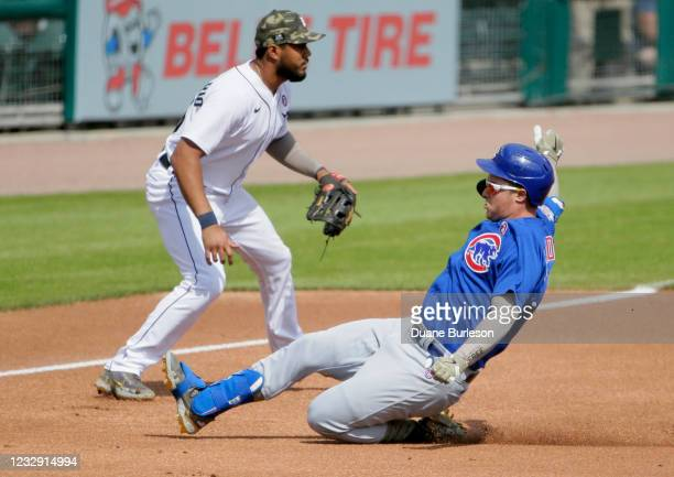 Joc Pederson of the Chicago Cubs slides past third baseman Jeimer Candelario of the Detroit Tigers for a triple during the first inning at Comerica...