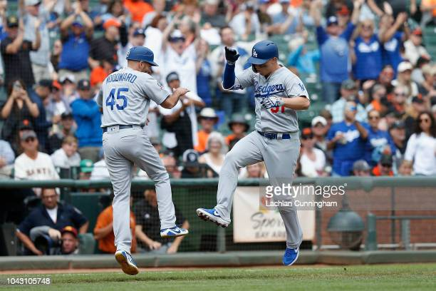 Joc Pederson of the Los Angeles Dodgers celebrates with third base coach Chris Woodward after hitting a leadoff home run in the top of the first...