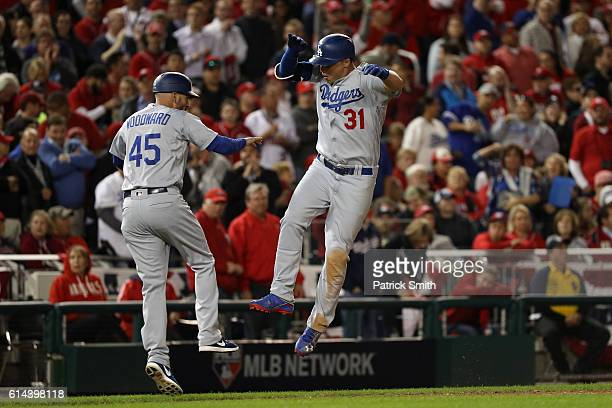 Joc Pederson of the Los Angeles Dodgers celebrates with third base coach Chris Woodward after hitting a solo home run in the seventh inning against...