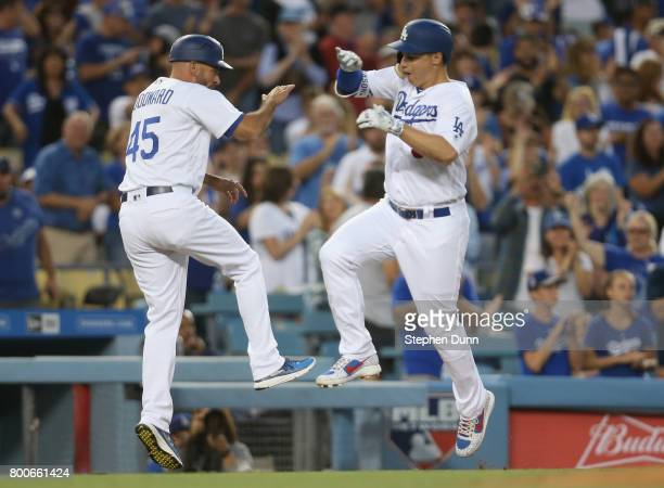 Joc Pederson of the Los Angeles Dodgers celebrates with third base coach Chris Woodward as he rounds third base after hitting a solo home run in the...