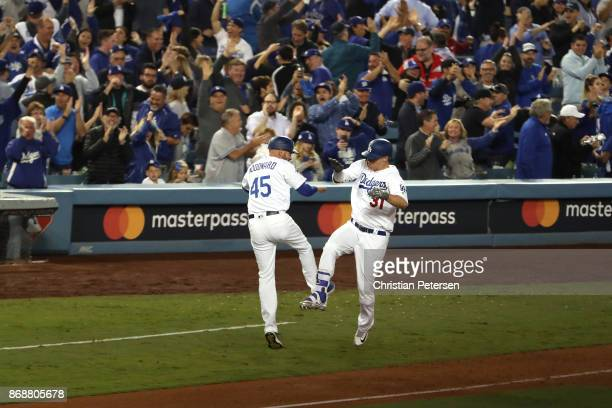 Joc Pederson of the Los Angeles Dodgers celebrates with third base coach Chris Woodward after hitting a solo home run during the seventh inning...