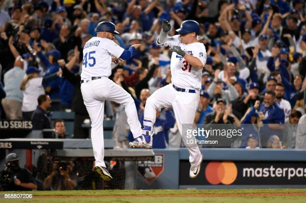 Joc Pederson of the Los Angeles Dodgers celebrates with third base coach Chris Woodward after hitting a solo home run in the seventh inning during...