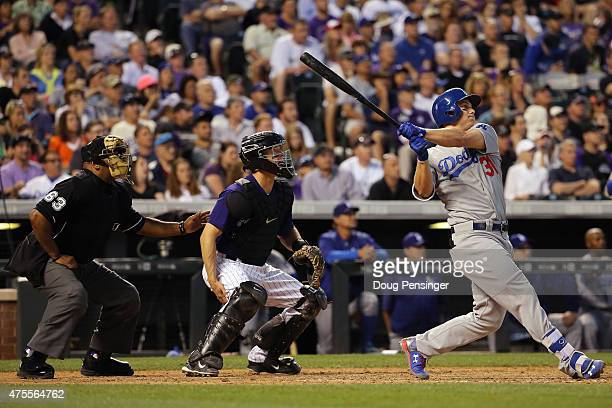 Joc Pederson of the Los Angeles Dodgers hits a three run home run off of Christian Friedrich of the Colorado Rockies as catcher Nick Hundley of the...