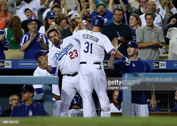 Joc Pederson of the Los Angeles Dodgers is greeted by Adrian Gonzalez as he returns to the dugout after hitting a solo home run in the seventh inning...