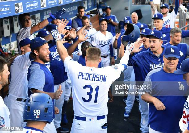 Joc Pederson of the Los Angeles Dodgers is greeted in the dugout after hitting a solo home run in the first inning against the San Diego Padres at...