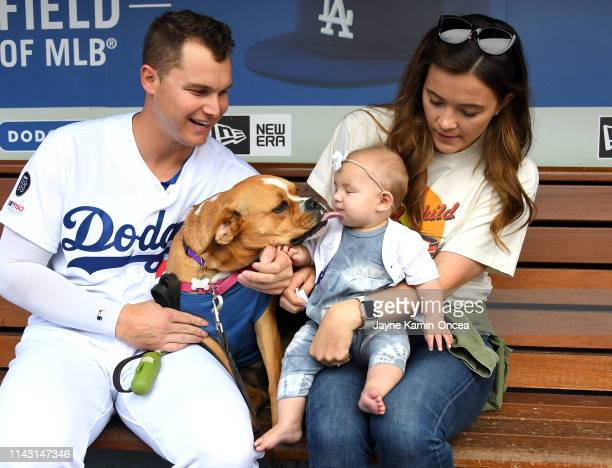 Joc Pederson of the Los Angeles Dodgers poses with his wife Kelsey dog Blue and daughter Poppy as more than 700 dogs attend the game between the Los...