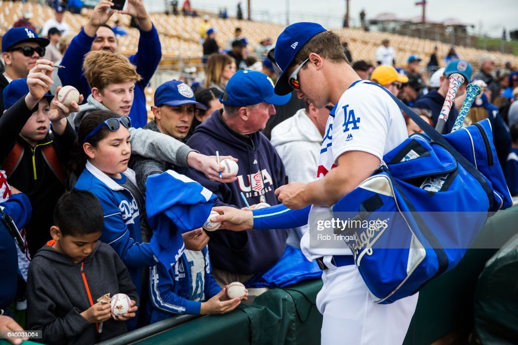 Joc Pederson #31 of the Los Angeles Dodgers signs autographs before a spring training game against the Colorado Rockies at Camelback Ranch on February 27, 2017 in Glendale, Arizona.