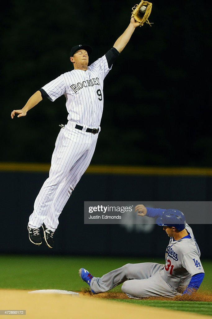 Joc Pederson #31 of the Los Angeles Dodgers slides in for a stolen base as second baseman DJ LeMahieu #9 of the Colorado Rockies has to jump to catch the baseball during the first inning at Coors Field on May 8, 2015 in Denver, Colorado.