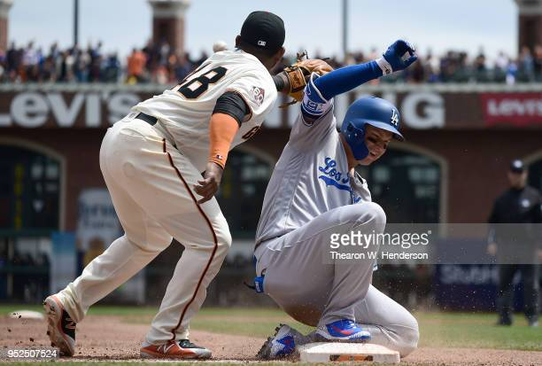 Joc Pederson of the Los Angeles Dodgers slides into third base with an RBI triple beating the throw to Pablo Sandoval of the San Francisco Giants in...